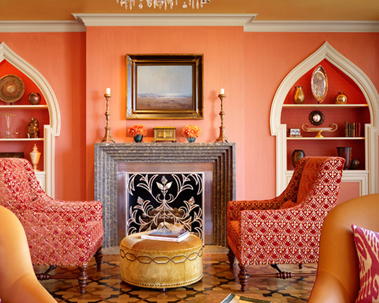 A papaya, coral, orange, sitting room with armchairs and ottoman.