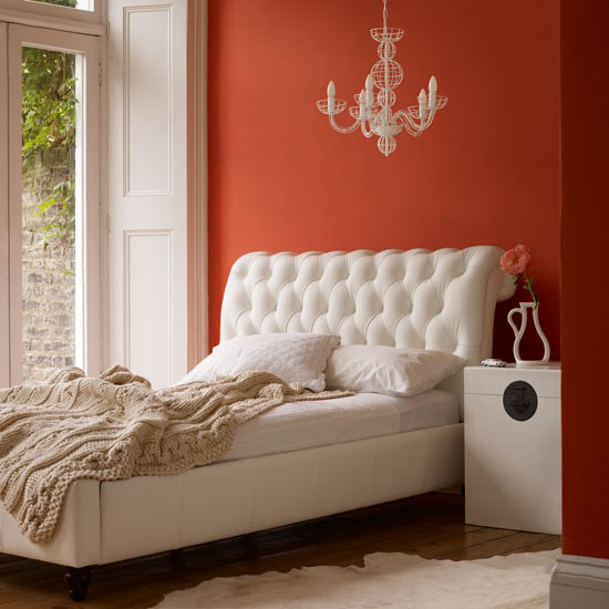 A papaya, coral, orange room interior with chaise.