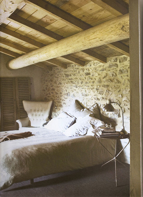 A modern earthy bedroom with exposed stone in a renovated barn in France.